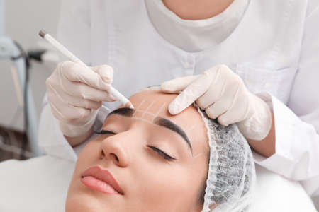 Young woman getting prepared for procedure of permanent eyebrow makeup in tattoo salon, closeup