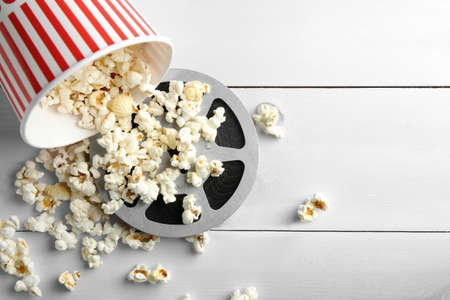 Tasty popcorn and movie reel on white wooden background