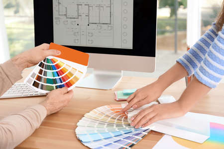 Designers with paint color palette samples at table, closeup