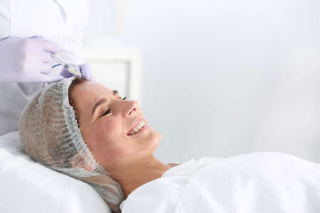 Woman undergoing face biorevitalization procedure in salon. Cosmetic treatment Foto de archivo
