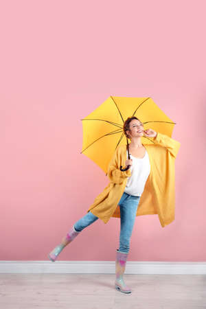 Woman with yellow umbrella near color wall Archivio Fotografico