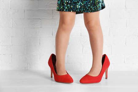 Klein meisje in oversized schoenen in de buurt van bakstenen muur, close-up op benen Stockfoto