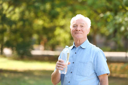 Elderly man with bottle of water outdoors on sunny day