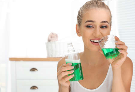 Woman holding bottle and glass with mouthwash in bathroom. Teeth care Stock Photo