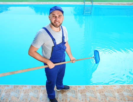 Male worker cleaning outdoor pool with scoop net Stockfoto