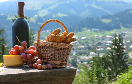 Bottle of red wine with ripe juicy grapes and other food for picnic on bench against mountain landscape