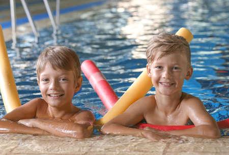Ragazzini con spaghetti di nuoto in piscina coperta