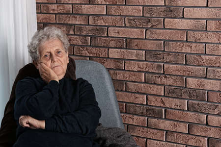 Poor elderly woman sitting on chair near brick wall. Space for text