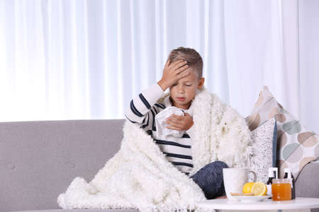 Ill boy suffering from cough on sofa at home Stock Photo