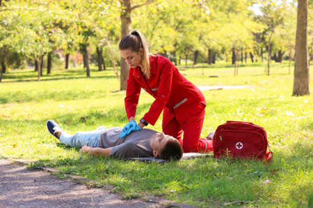 Woman in uniform performing CPR on unconscious man outdoors. First aid