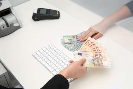 Kobieta wymienia pieniądze w oknie kasy, zbliżenie