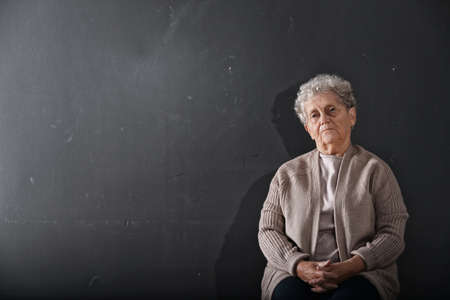 Portrait of poor elderly woman on dark background. Space for text
