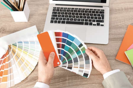 Male designer working with color palette at office table, closeup