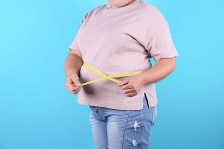 Fat woman with measuring tape on color background, closeup. Weight loss Standard-Bild