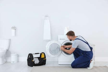 Young plumber fixing washing machine in bathroom 免版税图像 - 111301267