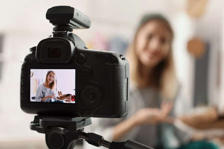 Fashion blogger recording video indoors, selective focus on camera display. Space for text Stock Photo