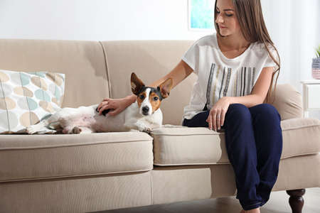 Beautiful woman with her dog sitting on sofa at home