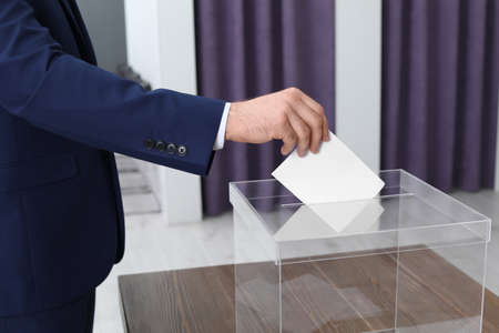 Man putting his vote into ballot box at polling station, closeup