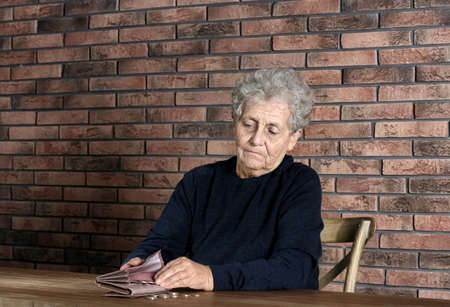 Poor elderly woman counting coins at table Stock Photo