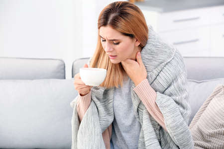 Woman with cup of tea for cough on sofa at home