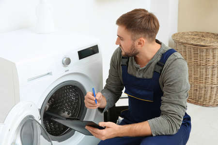 Young plumber with clipboard near washing machine in bathroom