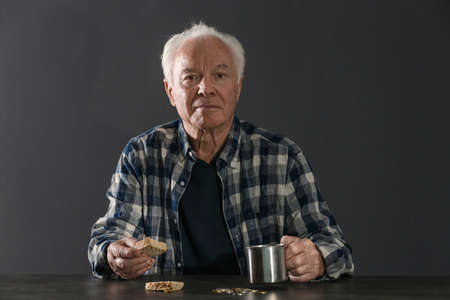 Poor elderly man with piece of bread and metal mug at table against dark background 版權商用圖片