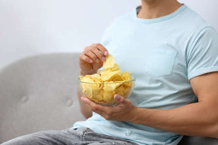 Man with bowl of potato chips on grey sofa, closeup