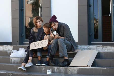 Poor homeless family begging and asking for help on city street 免版税图像