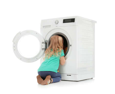 Cute little girl looking into washing machine with laundry on white background Reklamní fotografie