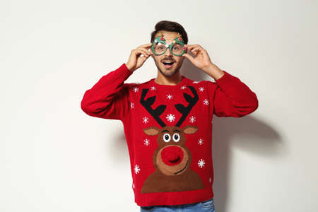 Young man in Christmas sweater with party glasses on white background Stockfoto