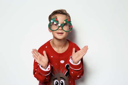 Netter kleiner Junge im Weihnachtspullover mit Partybrille auf weißem Hintergrund