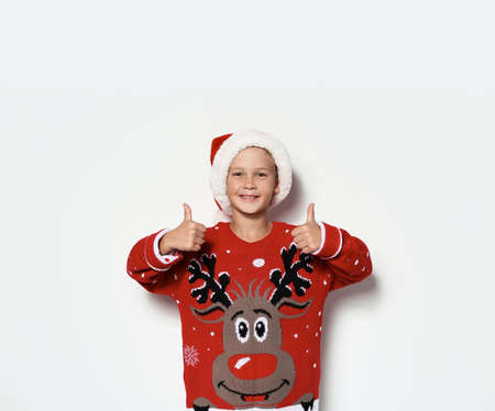 Cute little boy in Christmas sweater and hat on white background