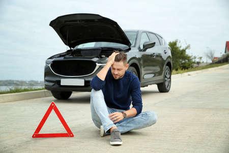 Upset man sitting near warning triangle and broken car on road Reklamní fotografie
