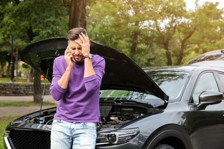 Man talking on phone near broken car outdoors Reklamní fotografie