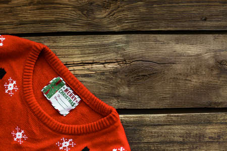 Christmas sweater with tag on wooden background, top view. Space for text Standard-Bild