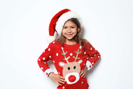 Cute little girl in Christmas sweater and hat on white background 写真素材