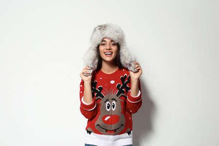 Junge Frau in Weihnachtspullover und Mütze auf weißem Hintergrund