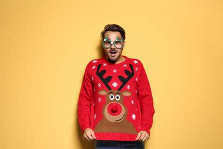 Giovane in maglione natalizio con occhiali da festa su sfondo colorato Archivio Fotografico
