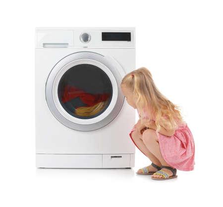 Cute little girl near washing machine with laundry on white background Reklamní fotografie