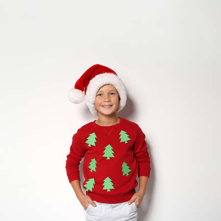 Cute little boy in handmade Christmas sweater and hat on white background Stock Photo