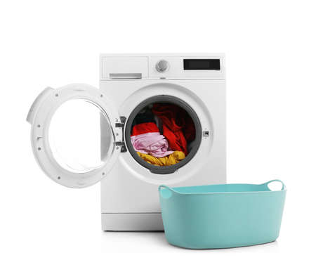 Modern washing machine with laundry and basket on white background Imagens