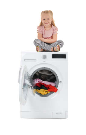 Cute little girl sitting on washing machine with laundry against white background