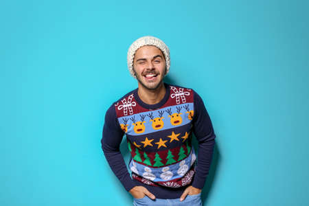 Young man in Christmas sweater and knitted hat on color background