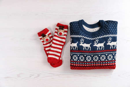 Christmas sweater and socks with pattern on wooden background, top view