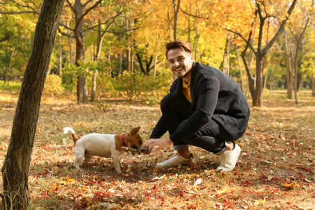 Young handsome man with his pet in park. Autumn walk Stock Photo