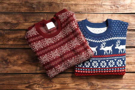 Christmas sweaters with pattern on wooden background, top view
