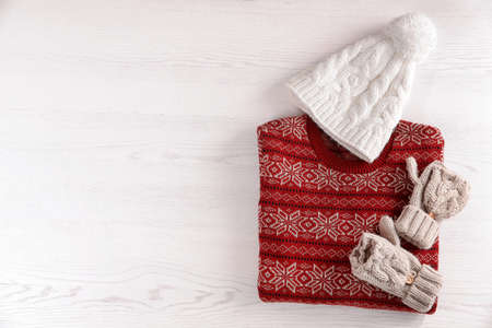 Mittens, hat and Christmas sweater with pattern on wooden background, top view. Space for text Stock Photo
