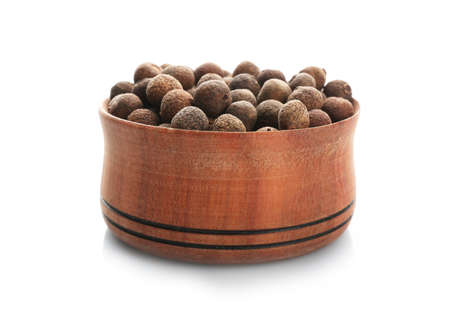 Wooden bowl with allspice pepper grains on white background