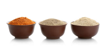 Bowls with different kinds of milled pepper on white background