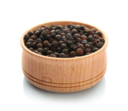 Wooden bowl with black pepper grains on white background